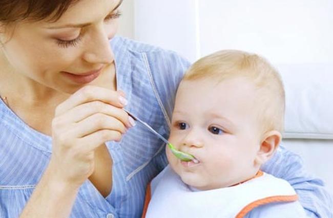 ребенка кормят с ложки